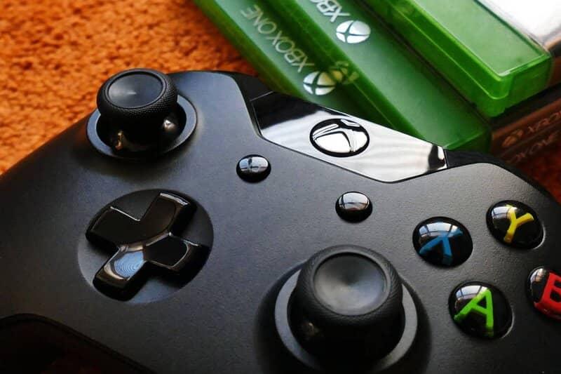 control de xbox junto a pila de juegos fisicos