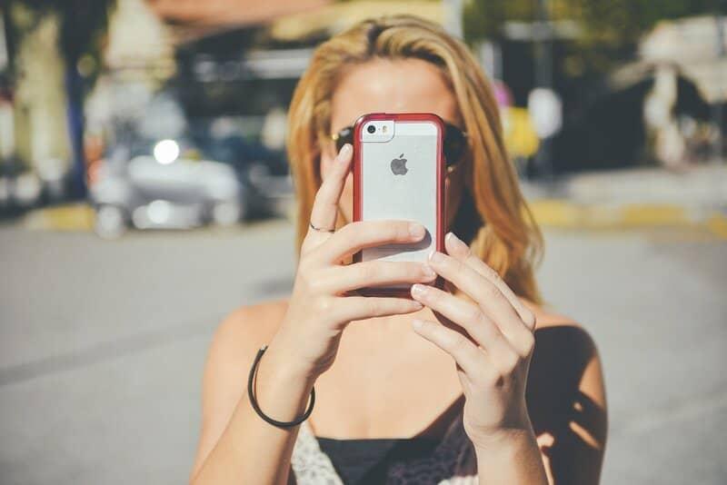 mujer tomando fotos en iphone para guardarlas en icloud