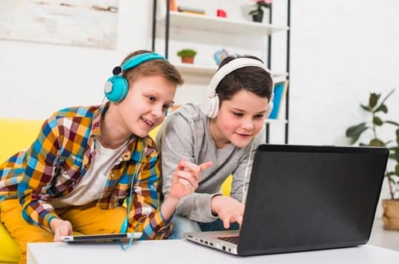 two children playing on a laptop