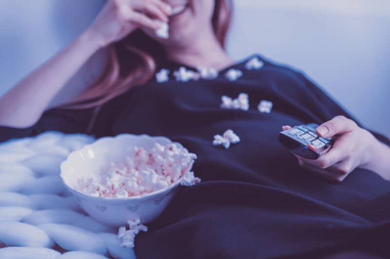 mujer acostada y comiendo mientras ve hbo