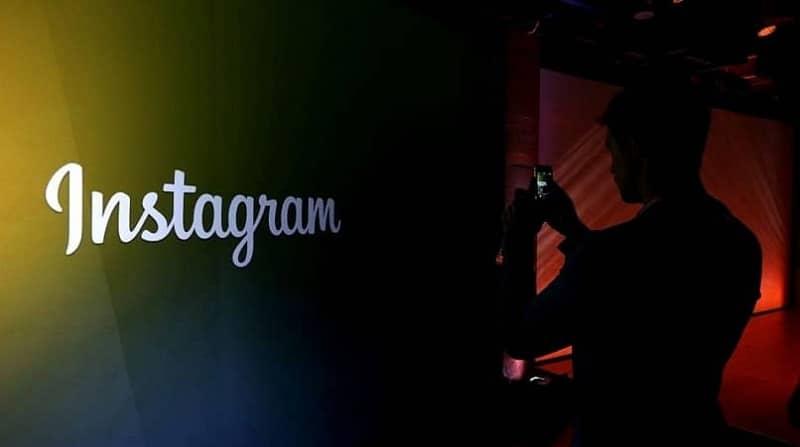 hombre tomando foto al logo de instagram