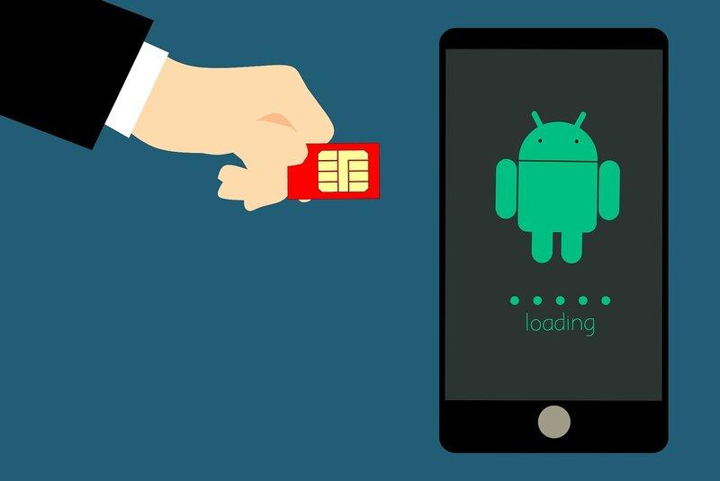 mano con simcard y un telefono android al lado