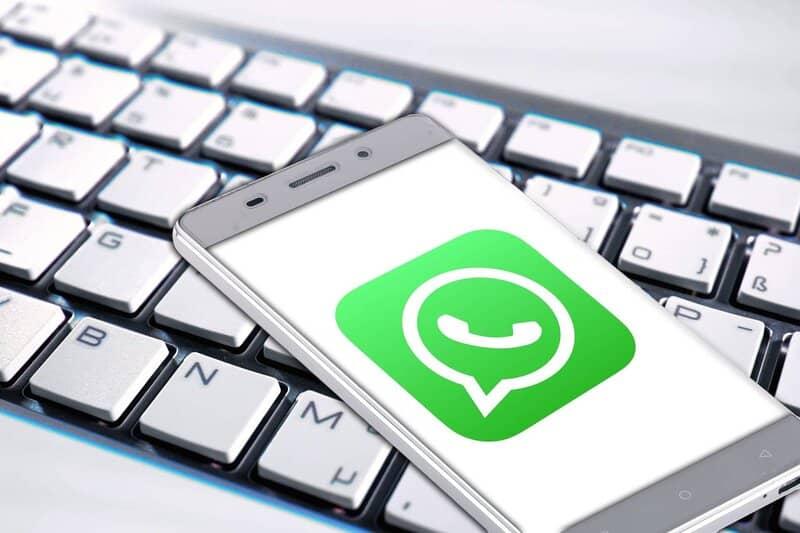 telefeno encima de teclado con whatsapp iniciando