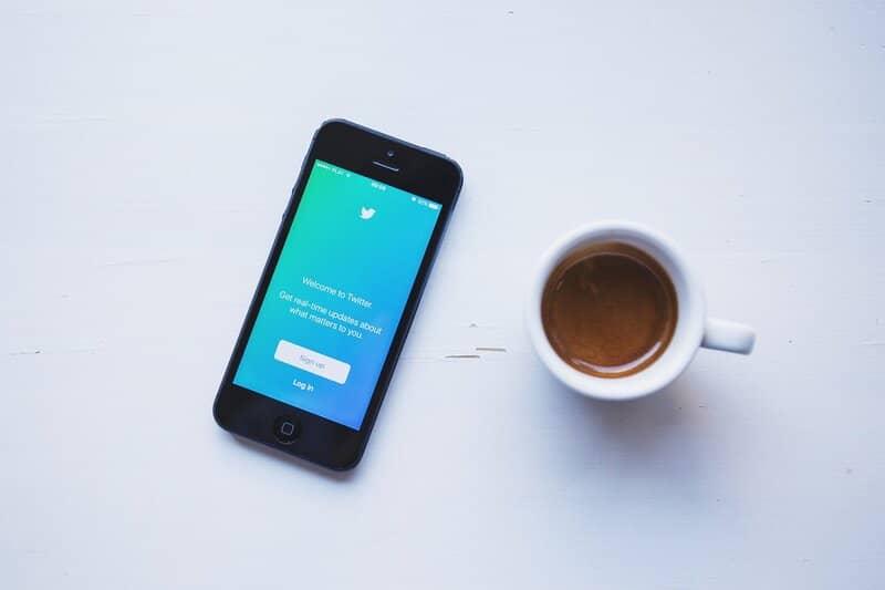 telefono junto a cafe iniciando la aplicacion de twitter
